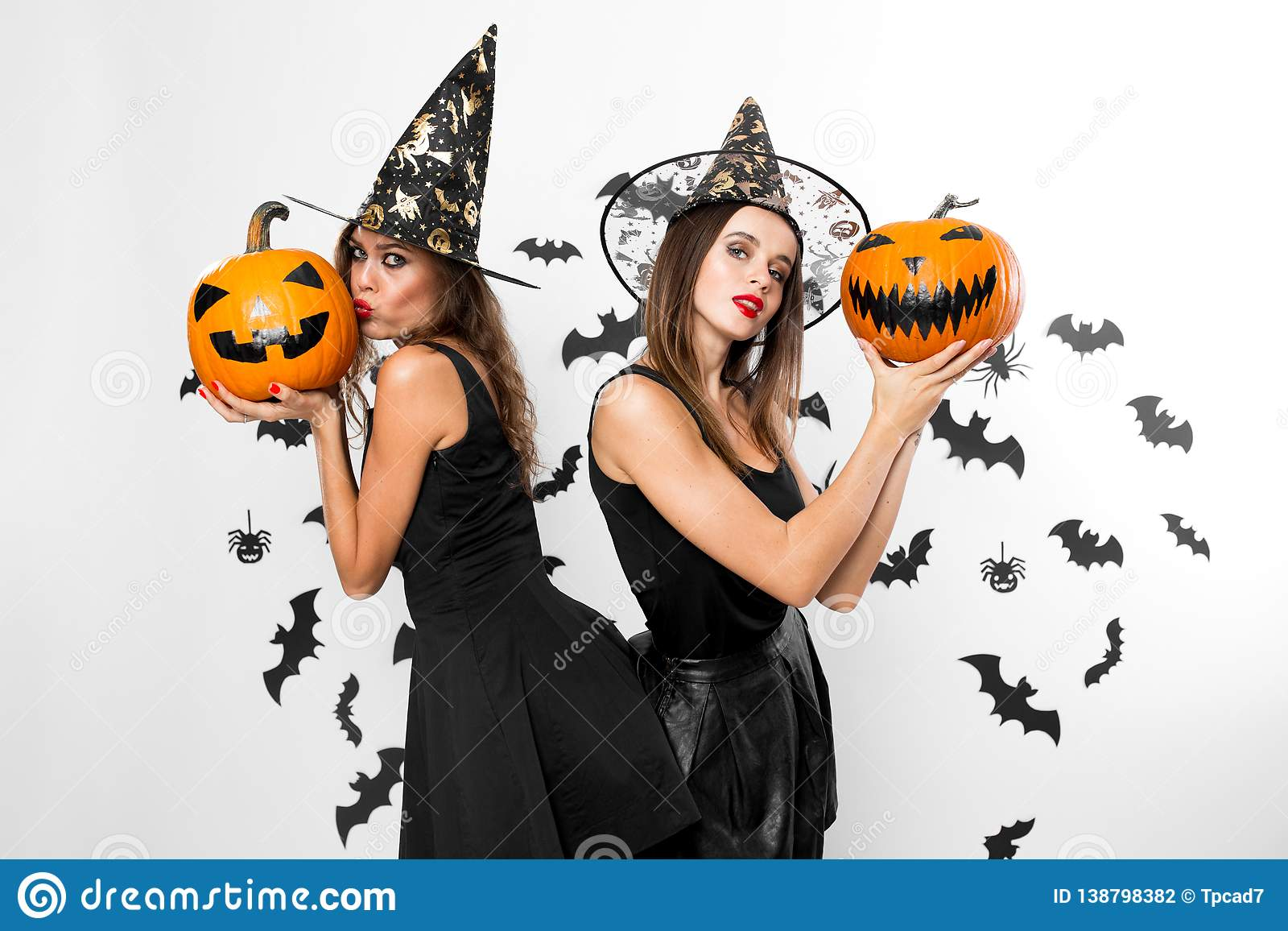 Two brunette girls in black dresses and witch hats hold halloween pumpkins  on the background of