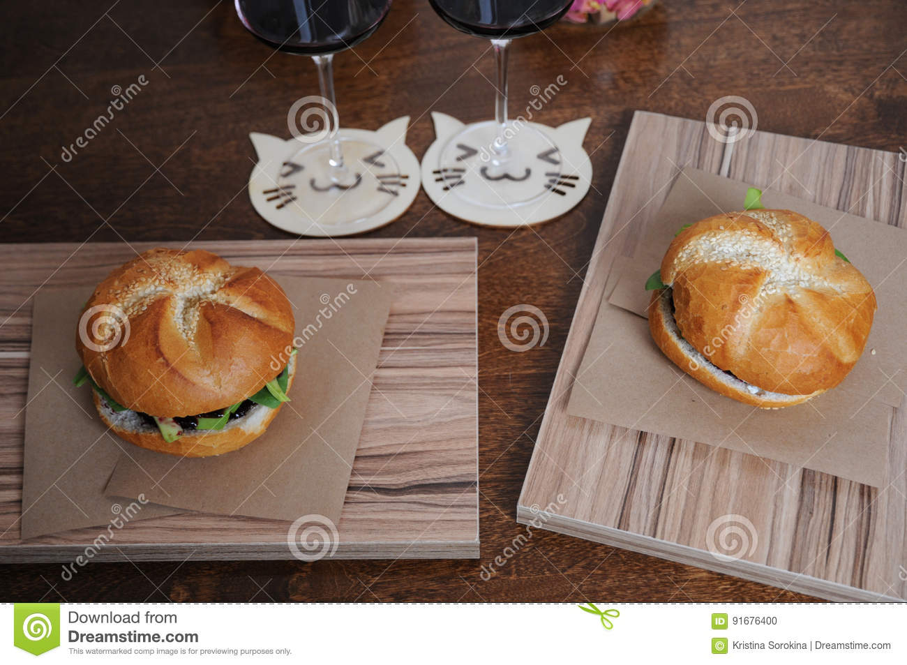 Two Burgers On Kraft Paper On Zebrano Boards And Two Glasses With