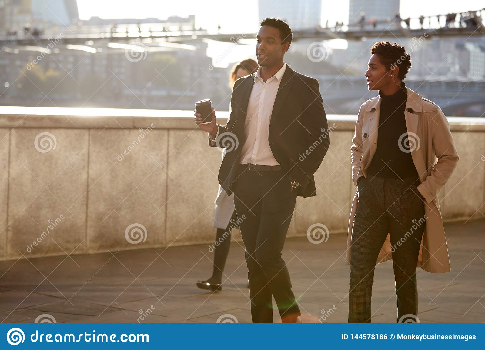Two business colleagues walking by the Thames riverside in the city of London talking, man holding takeaway coffee