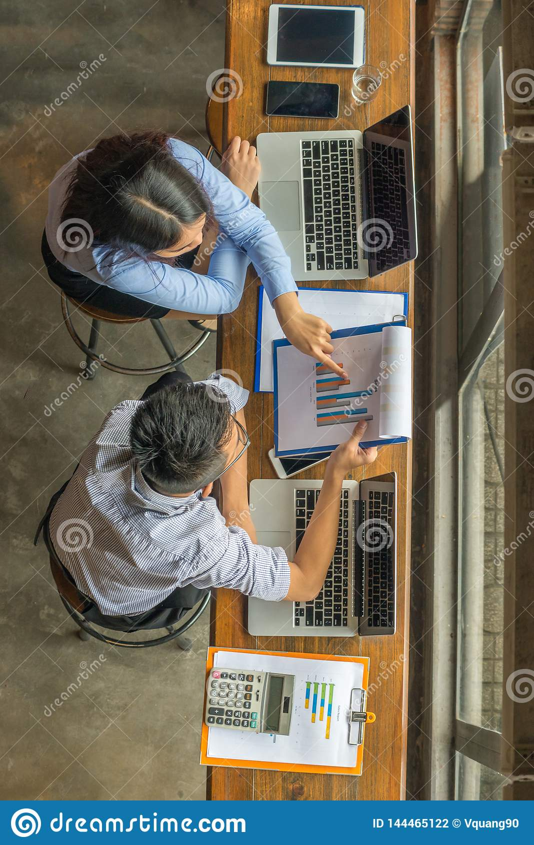 Two business employees discuss about financial data on report