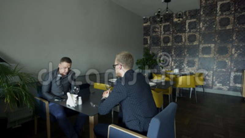 Two Business Men Sit In A Stylish Cafe At A Table Stock Footage - Table talk menu
