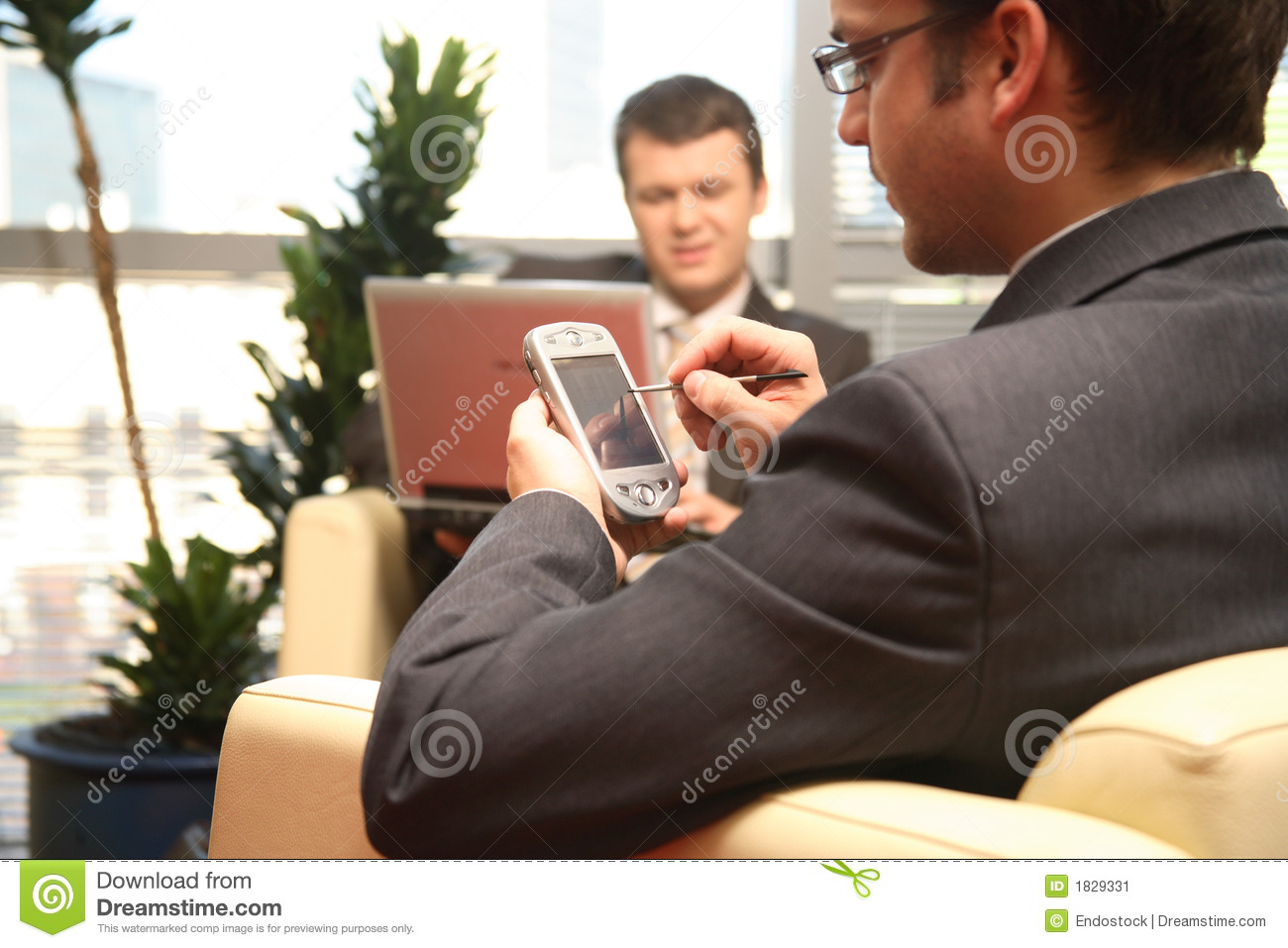 Two business men working with laptop & palmtop in the office environment.