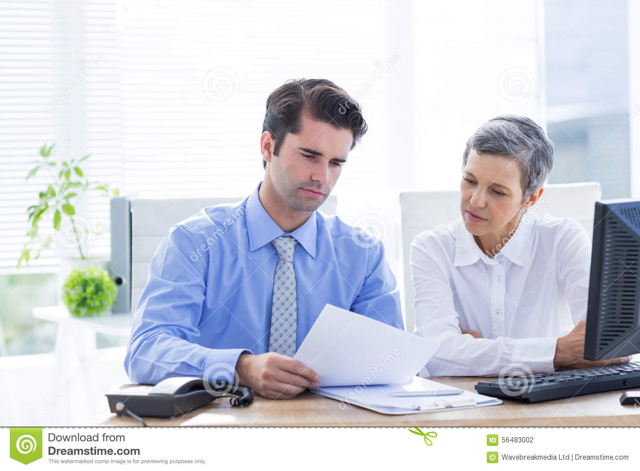 Two Business People Looking At A Paper While Working On ...