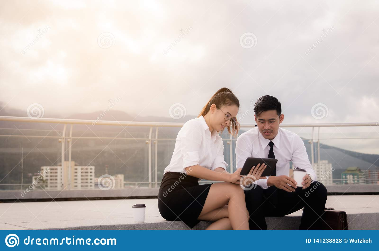Two business people sitting on roof floor and using digital tablet at outside business office together