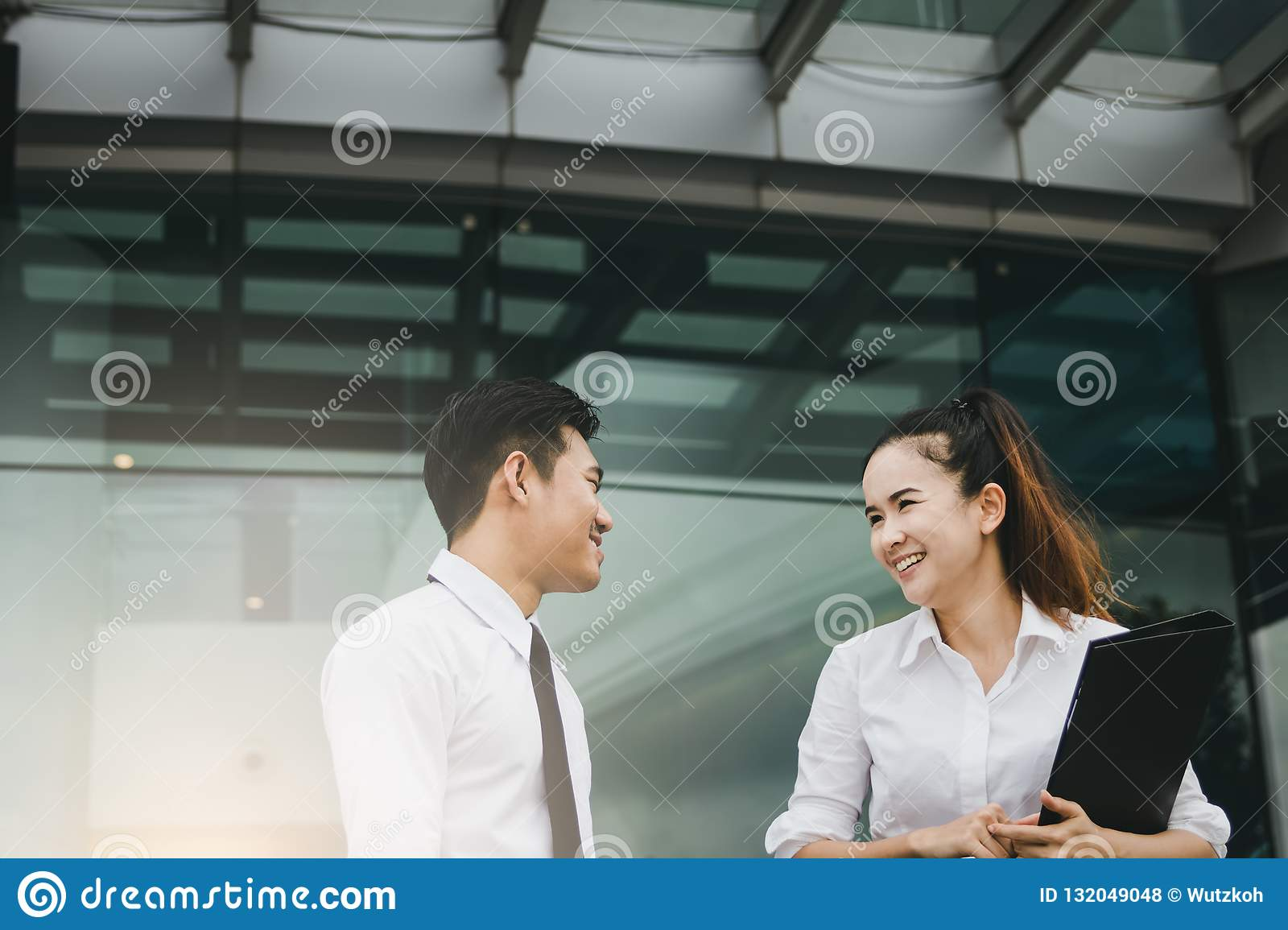 Two business people talking together at office building.