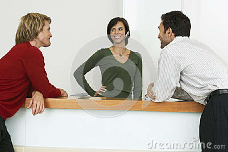 Two Businessmen Flirting With Receptionist At Reception Desk, Smiling Stock Image ...