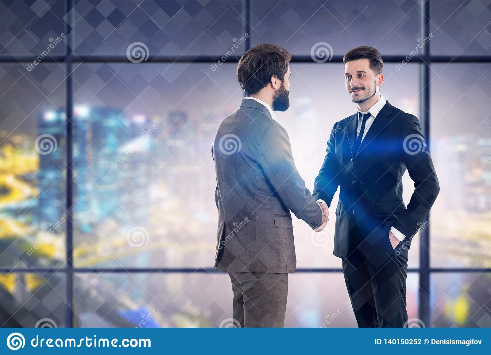 Two businessmen shaking hands in night office