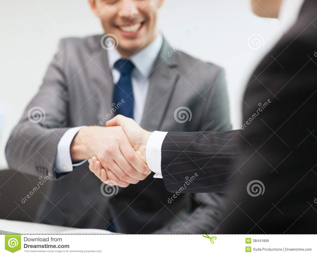 two businessmen shaking hands in office royalty free stock