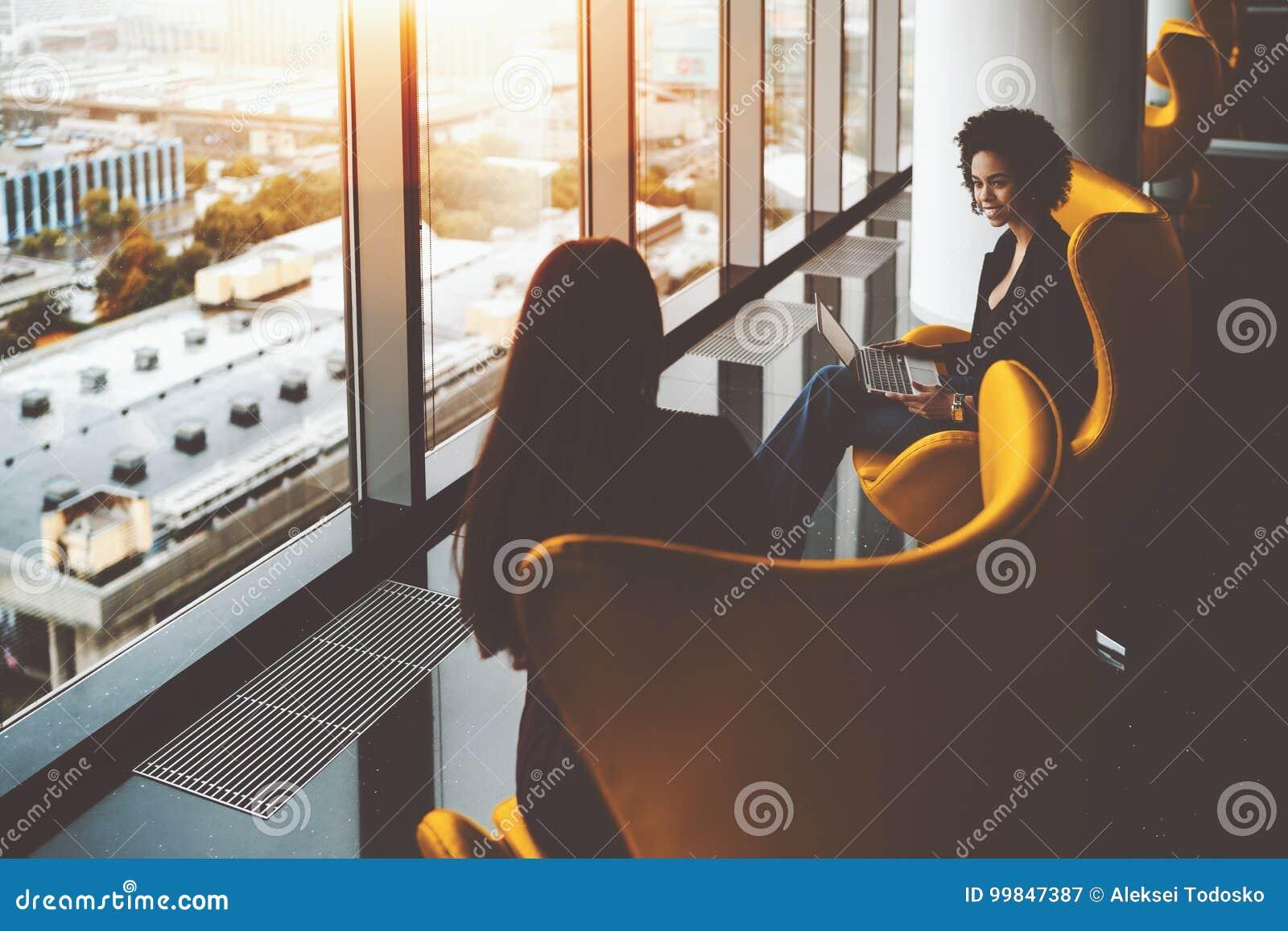Two businesswomen having work meeting near office windows