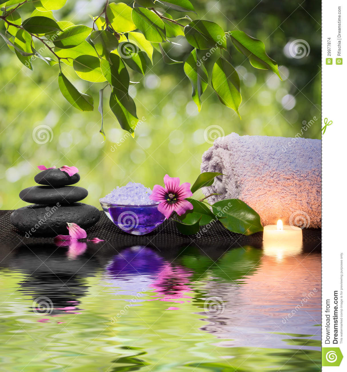 two candles and towels black stones and purple flower on