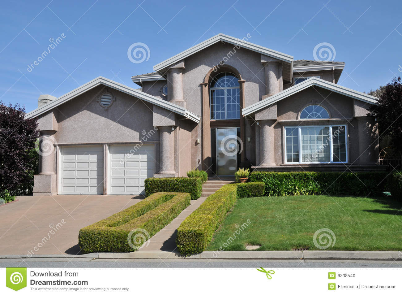 Two Car Garage House With Decorative Schrubs Stock Photo