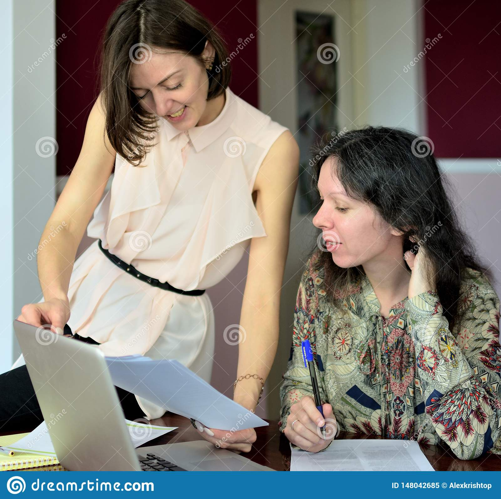 Two casually dressed young ladies models sit on a desk in a vintage office and discuss model release documents