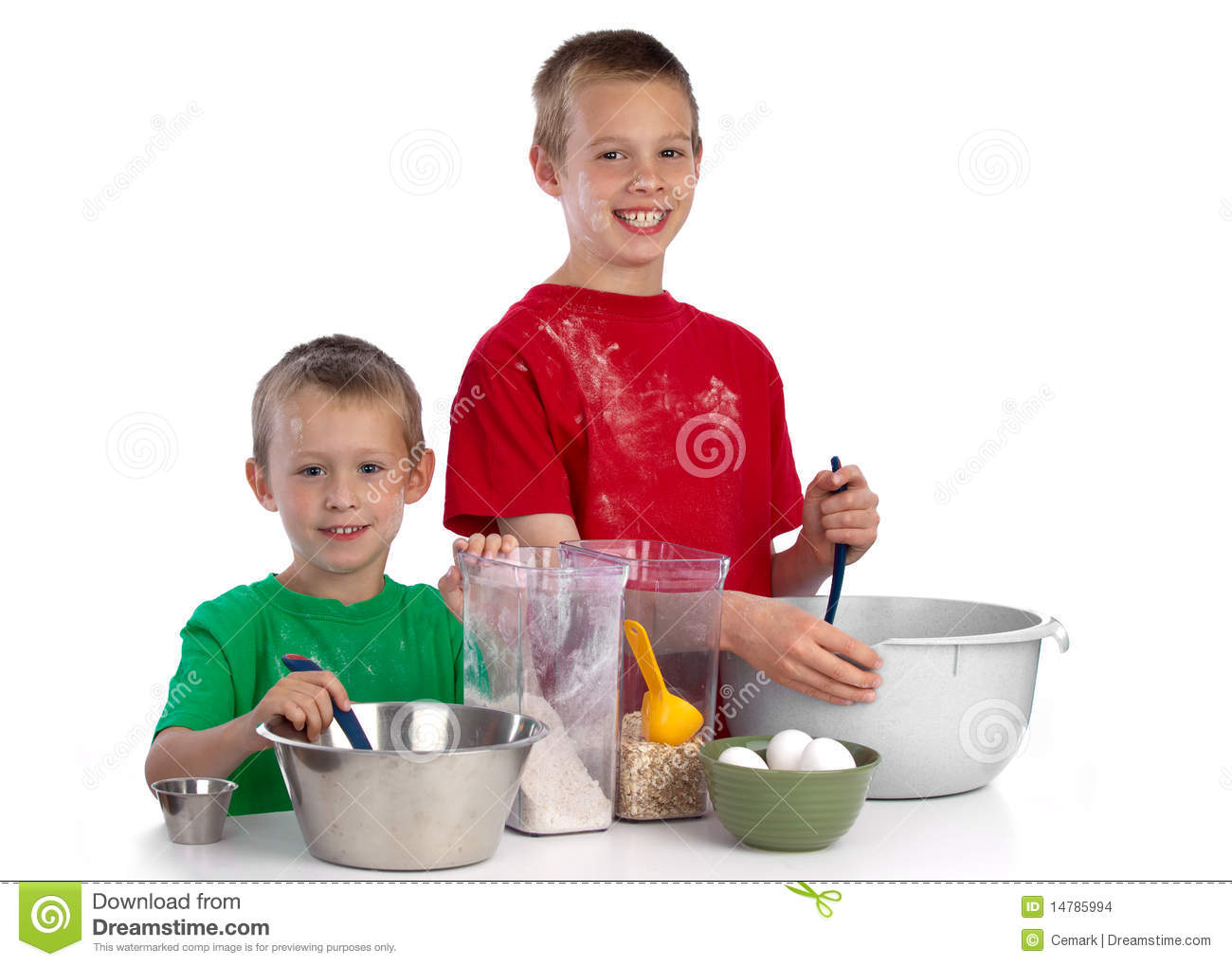 Two caucasian brothers baking a cake