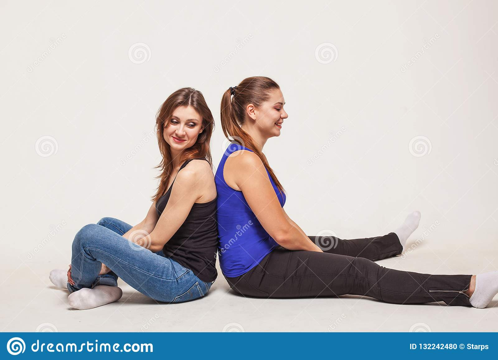 Two young women sit back to back