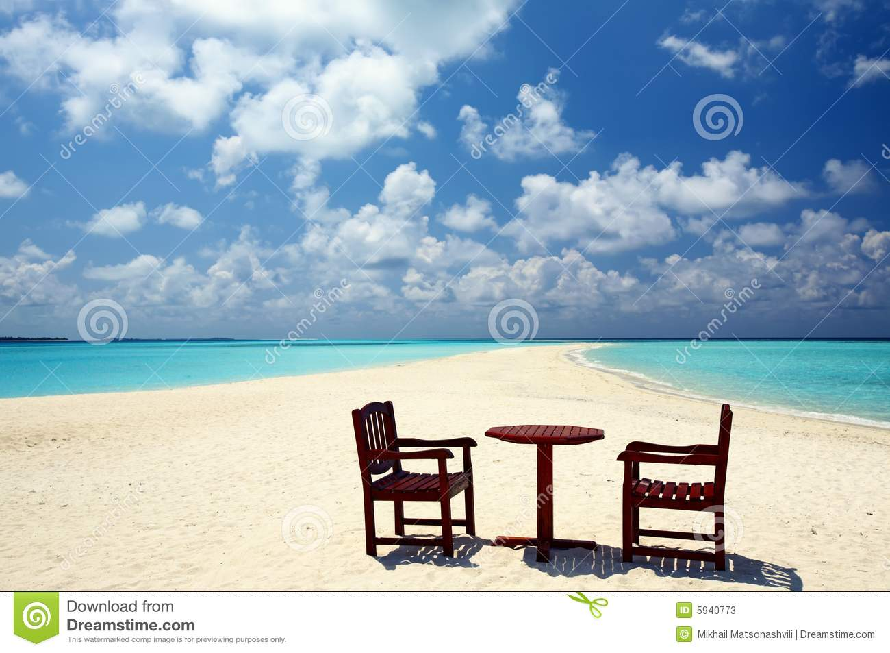 Two chairs and one table are on a beach