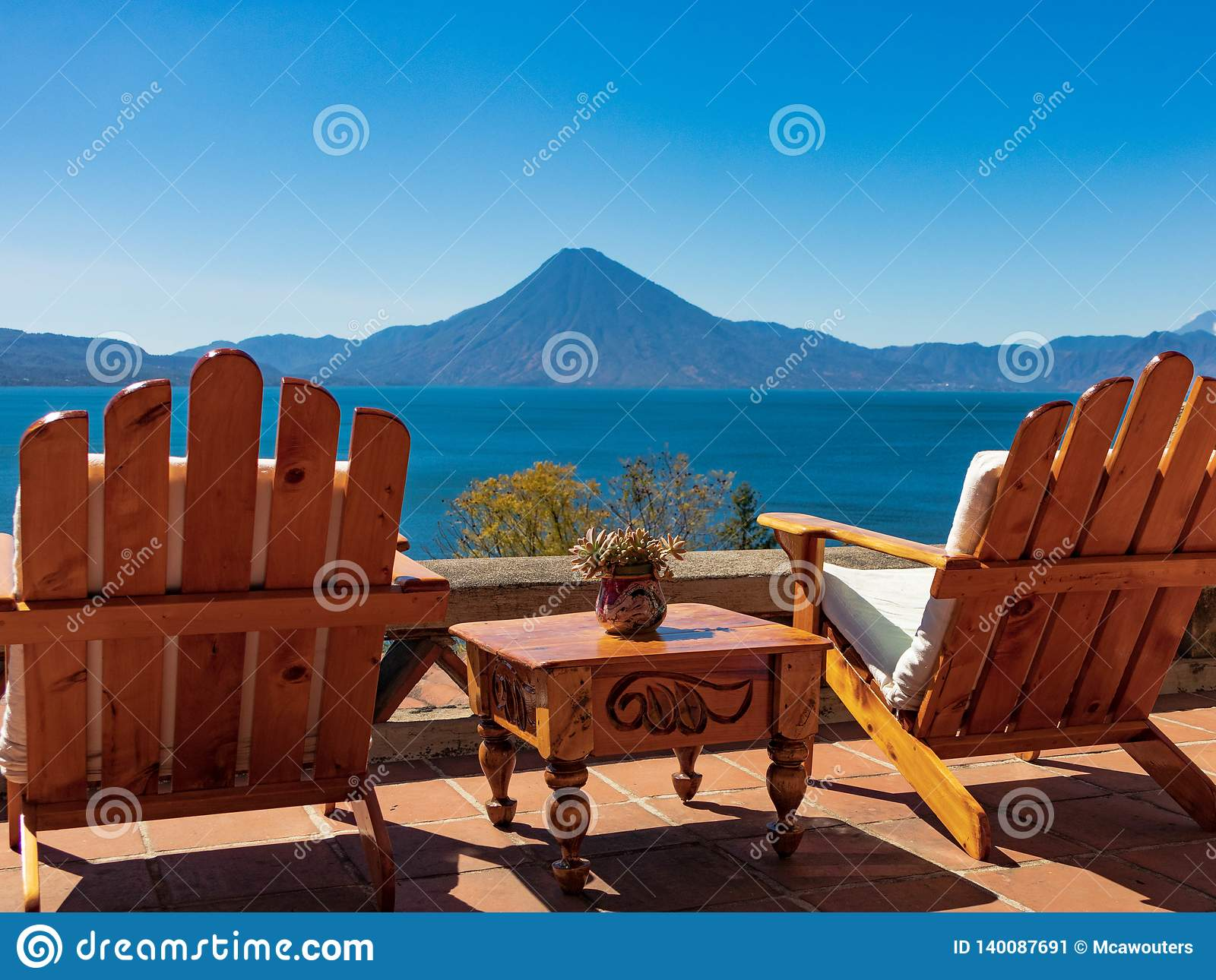 Two chairs with table looking out over lake and volcano