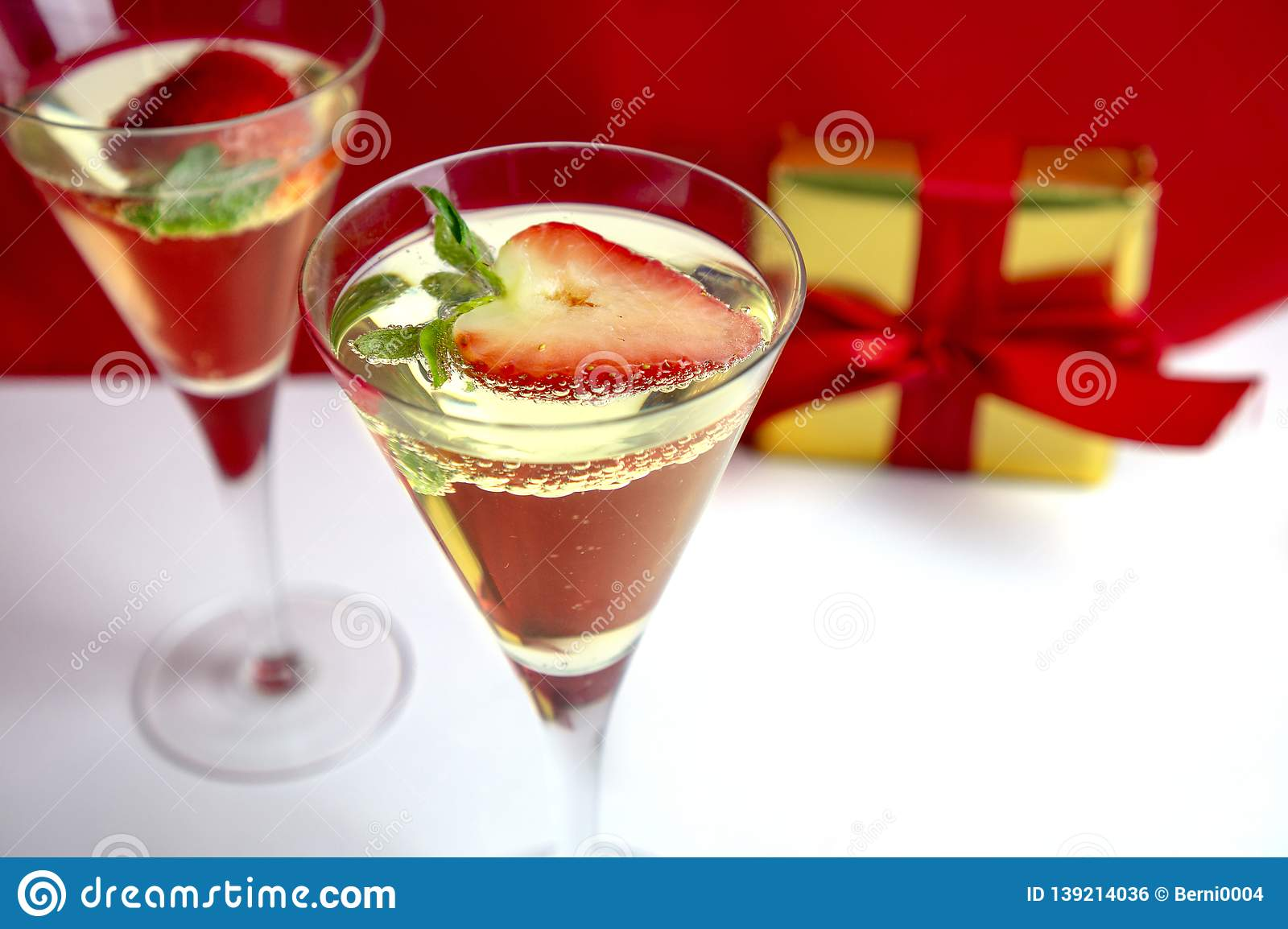 Two champagne glasses with heart shaped strawberry and a gift in the background Valentine`s Day concept