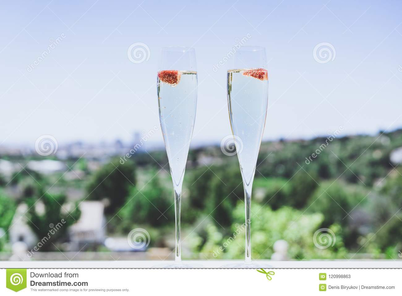 Two champagne glasses with strawberry on sunny terrace outdoor patio overlooking clean blue sky at summer day outside of