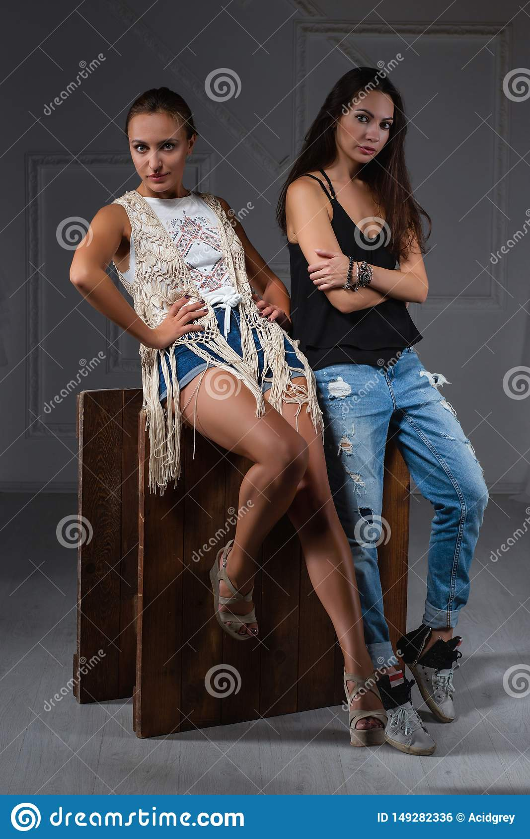 Two charming lady posing in a studio