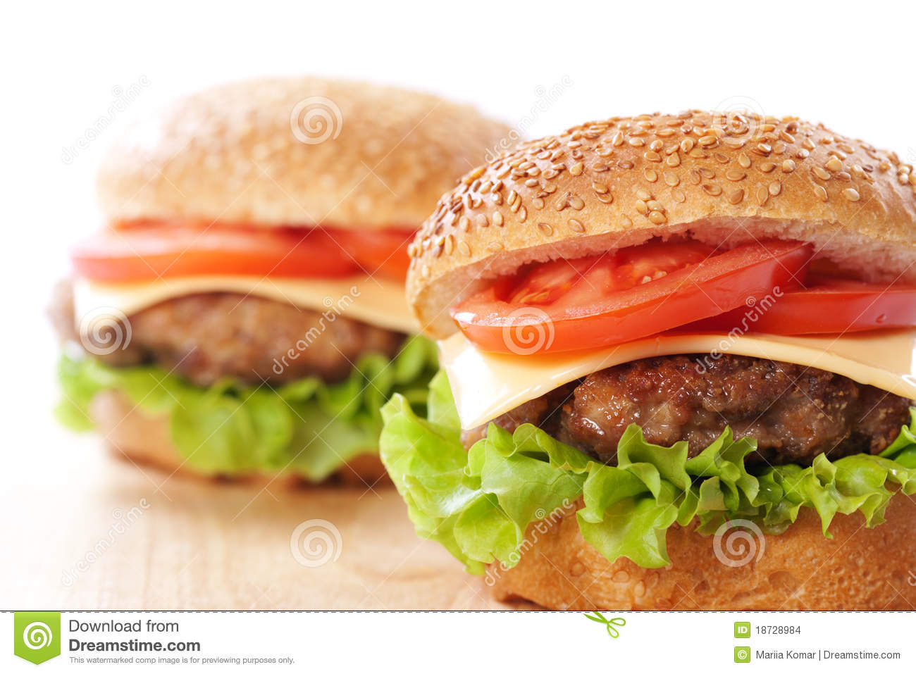 Two cheeseburgers with tomatoes and lettuce on a wooden table.
