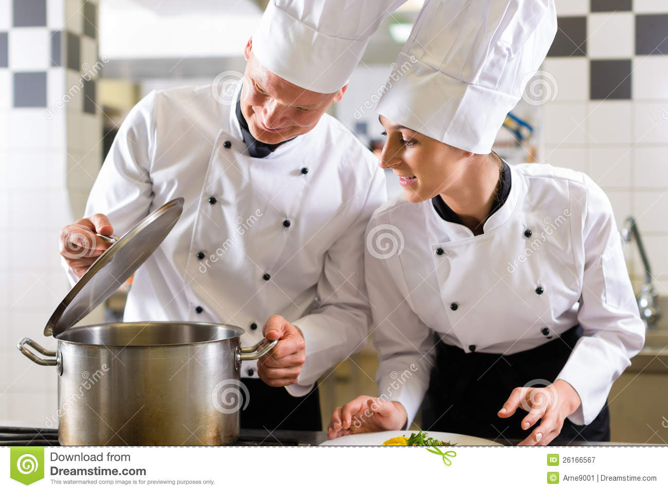 two chefs man and woman in hotel or restaurant kitchen working and