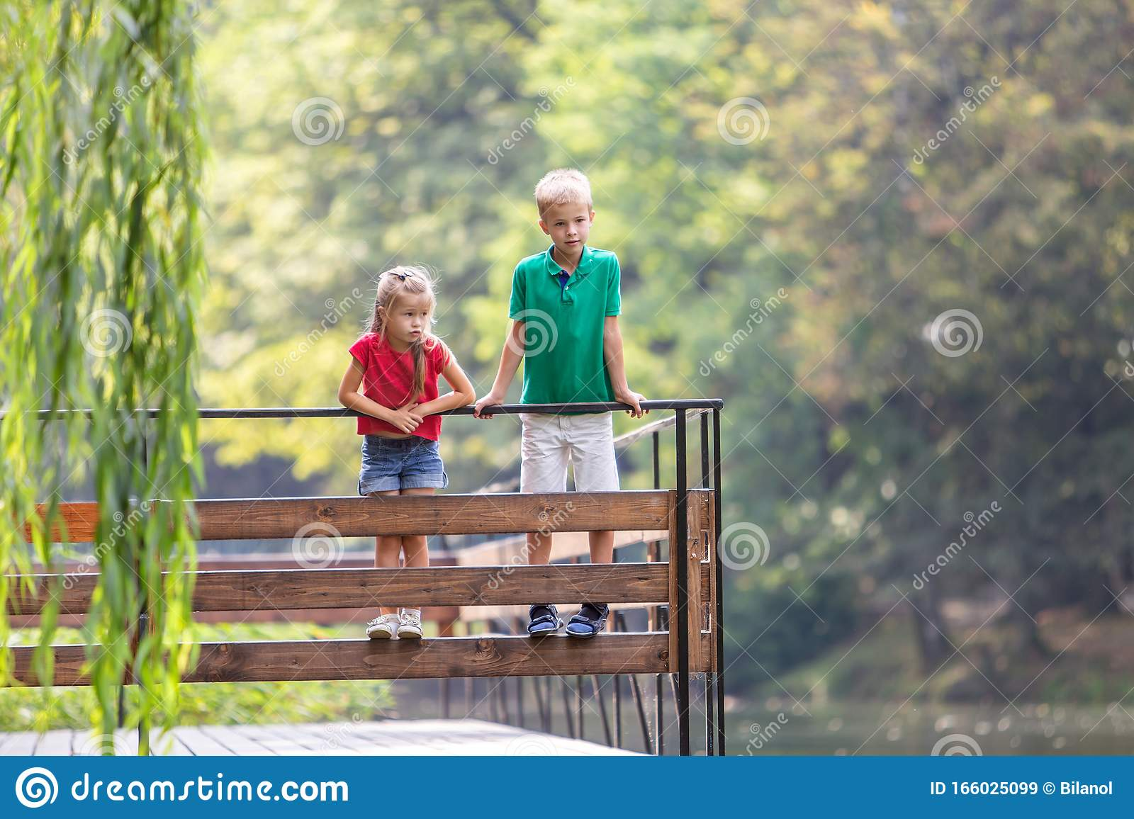 Two Children Boy And Girl Standing On Wooden Deck On A ...
