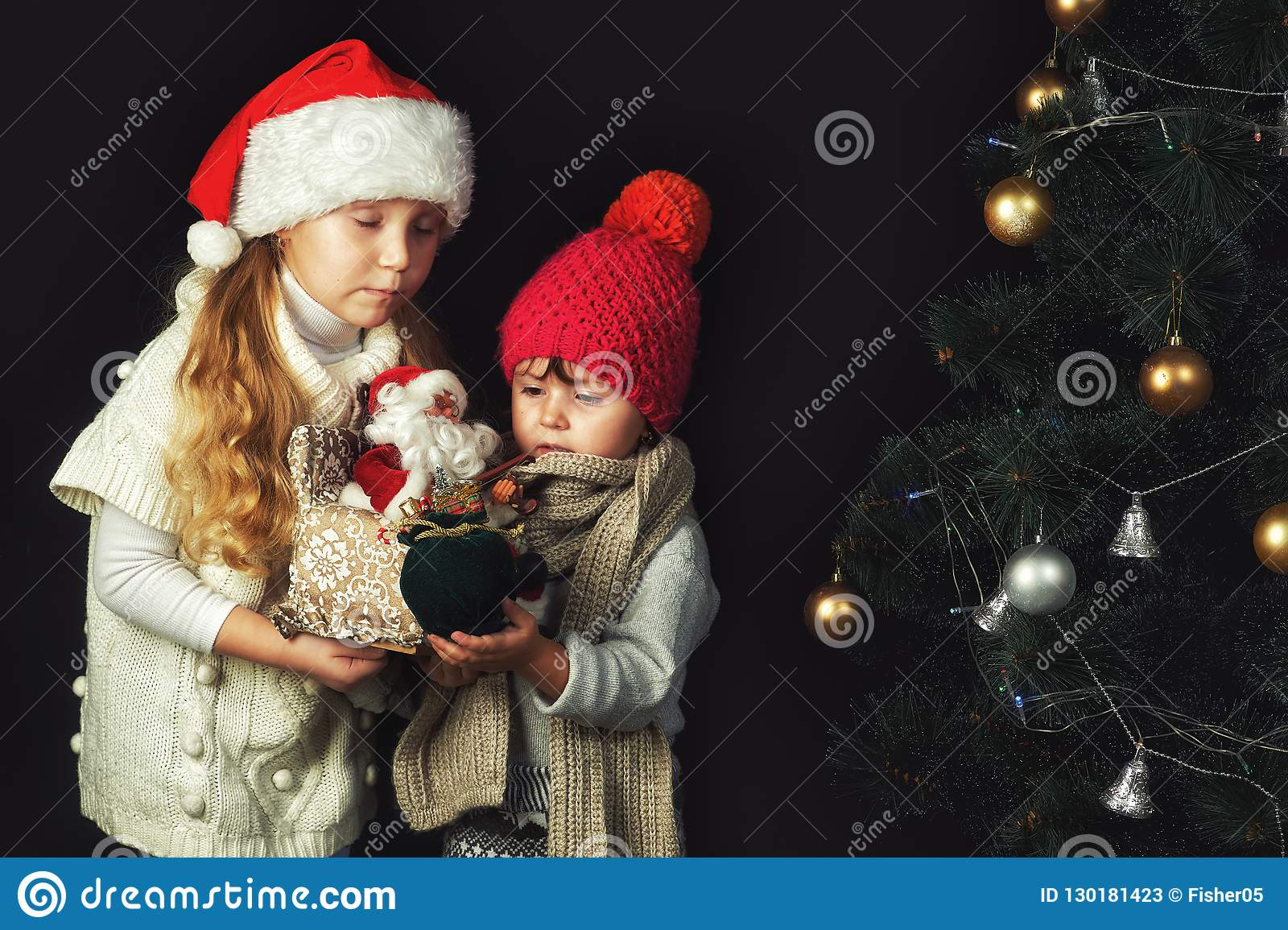 Two Children At The Christmas Tree Girls In Warm Sweaters And Hats Stock Image Image Of Baby Place 130181423