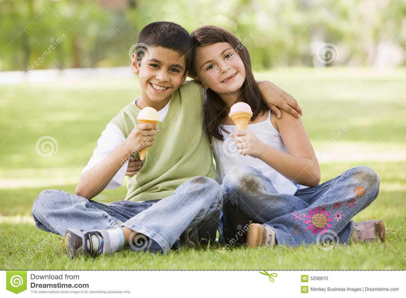 Two children eating ice cream in park