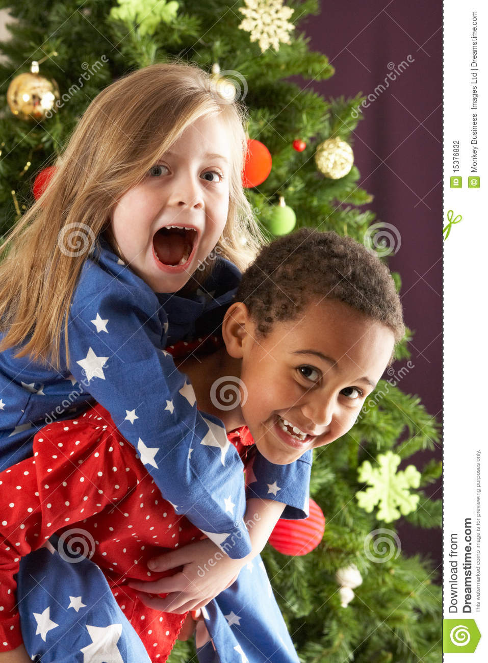 two children having fun in front of christmas tree stock