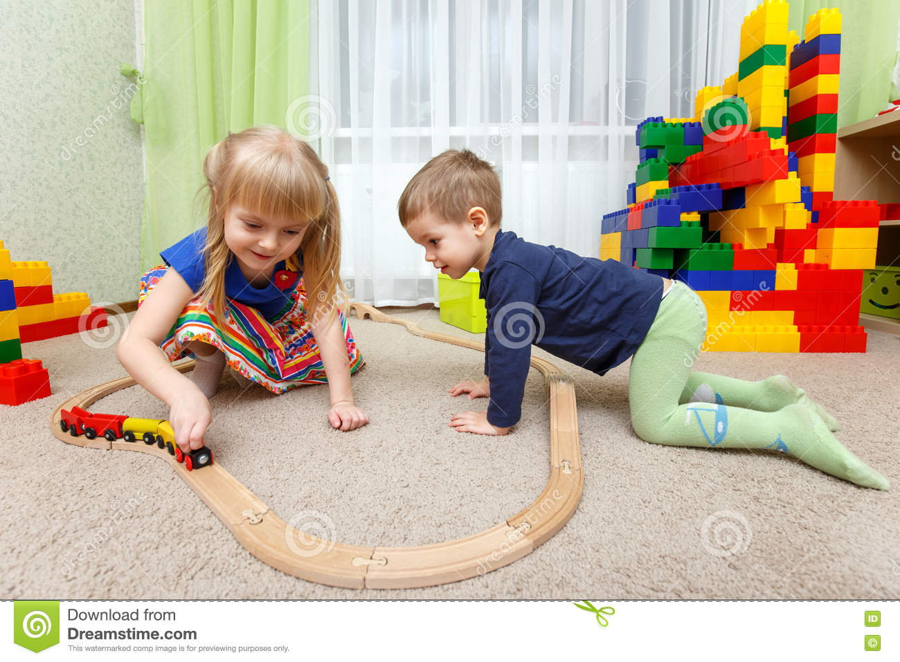 Toys For Kindergarten : Two children play with toy railway in kindergarten stock