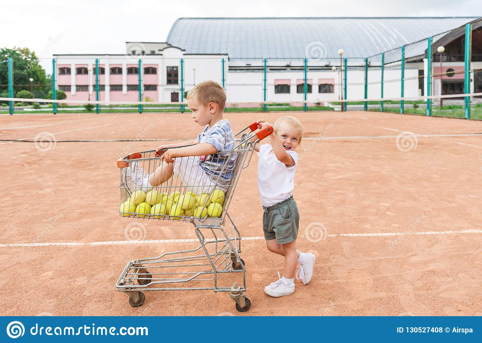 Two children playing on tennis court. Little boy and tennis balls in the shopping cart.