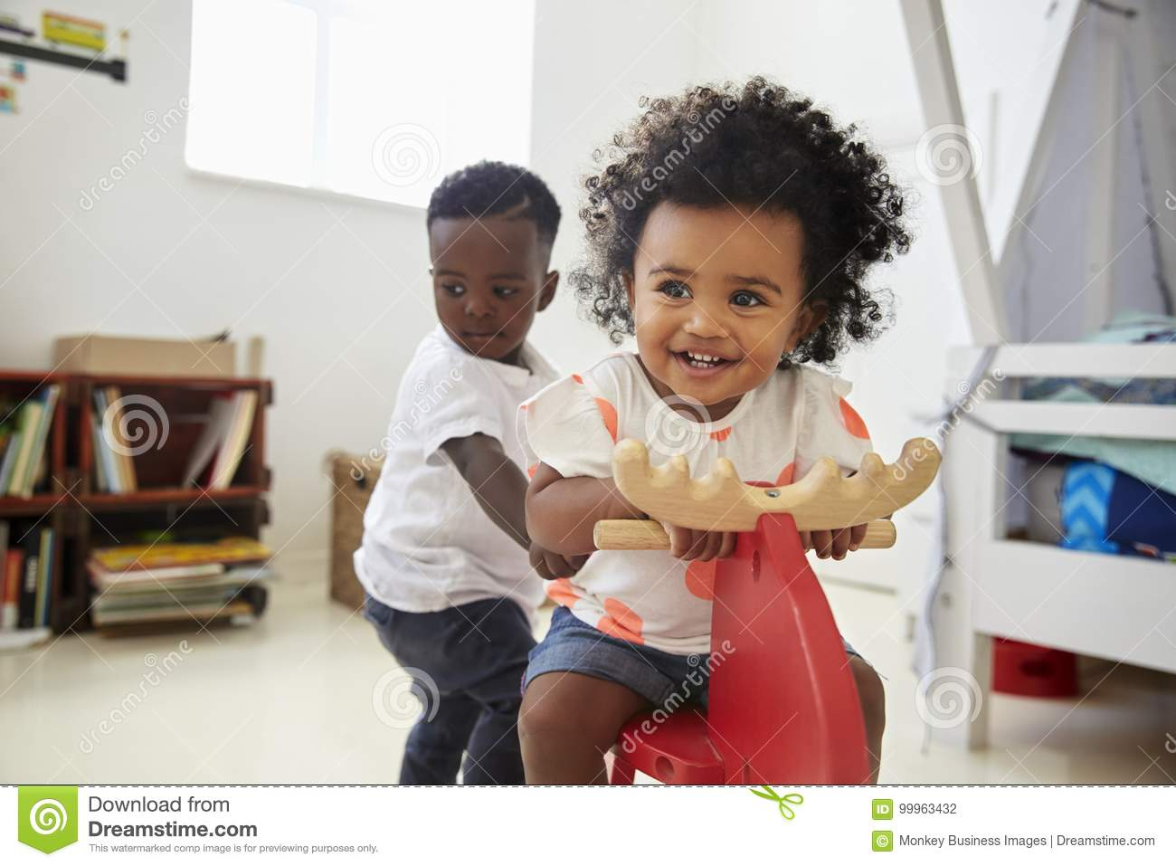 Two Children Sitting On Ride On Toy In Playroom