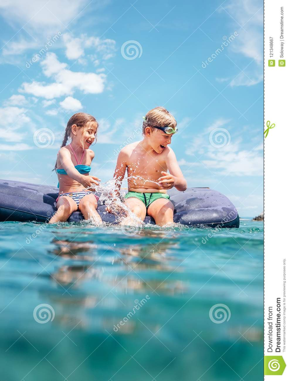 Two childs, sister and brother, have fun when swim on inflatable