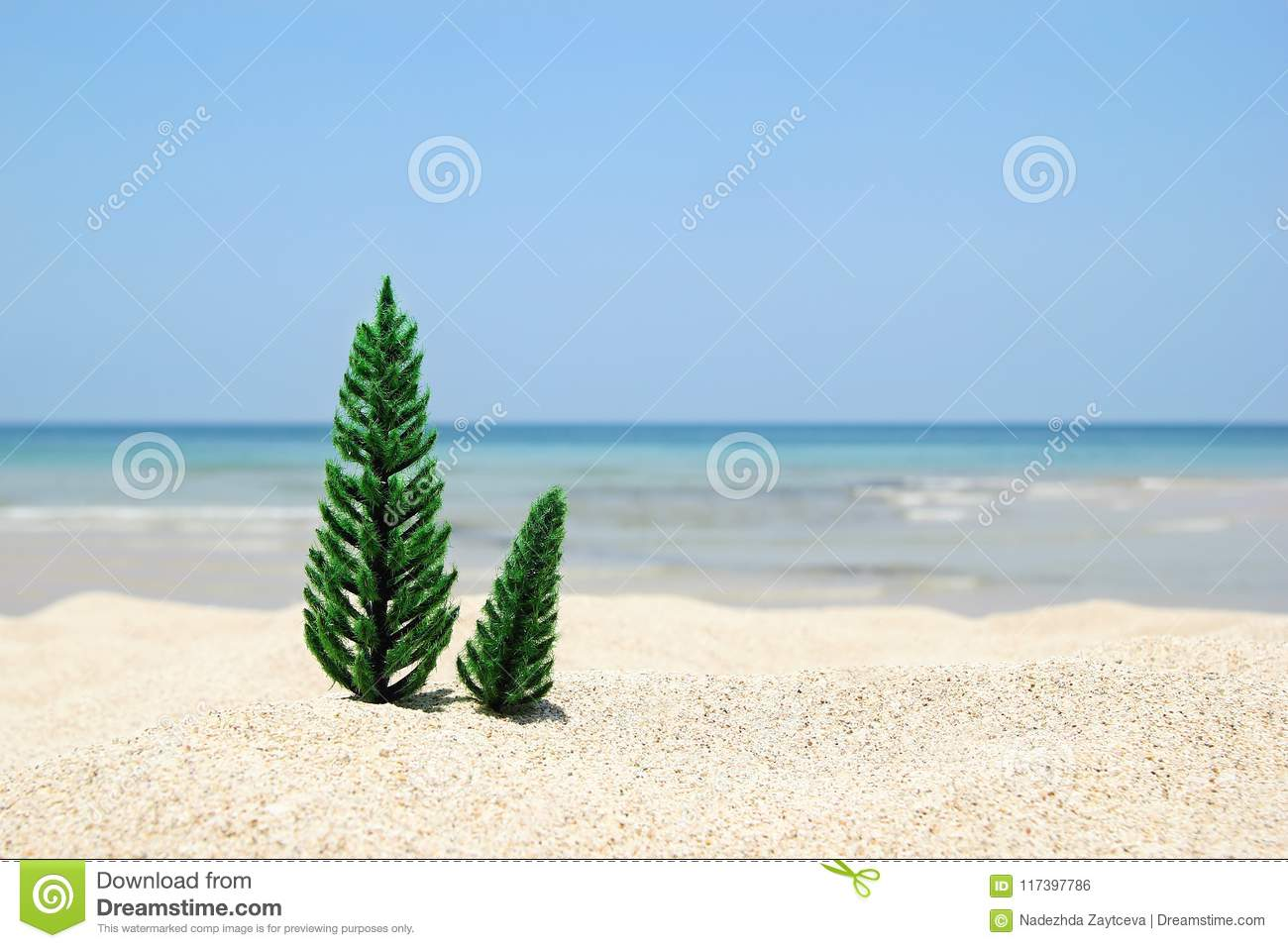 Two Christmas trees on the white sand beach on the background of blue sea and sky on a sunny day.