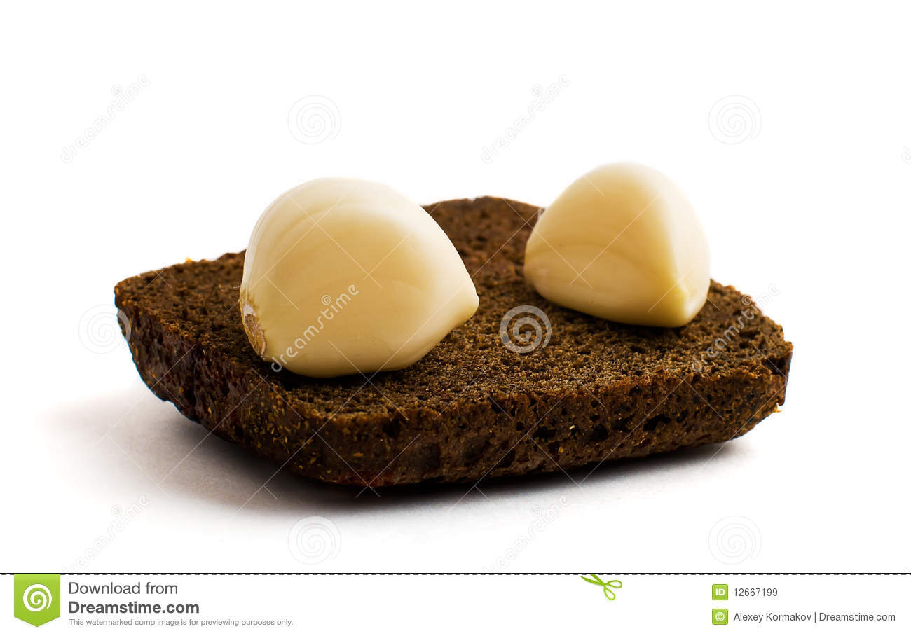 Two Cloves Of Garlic On A Piece Of Black Bread Royalty ...