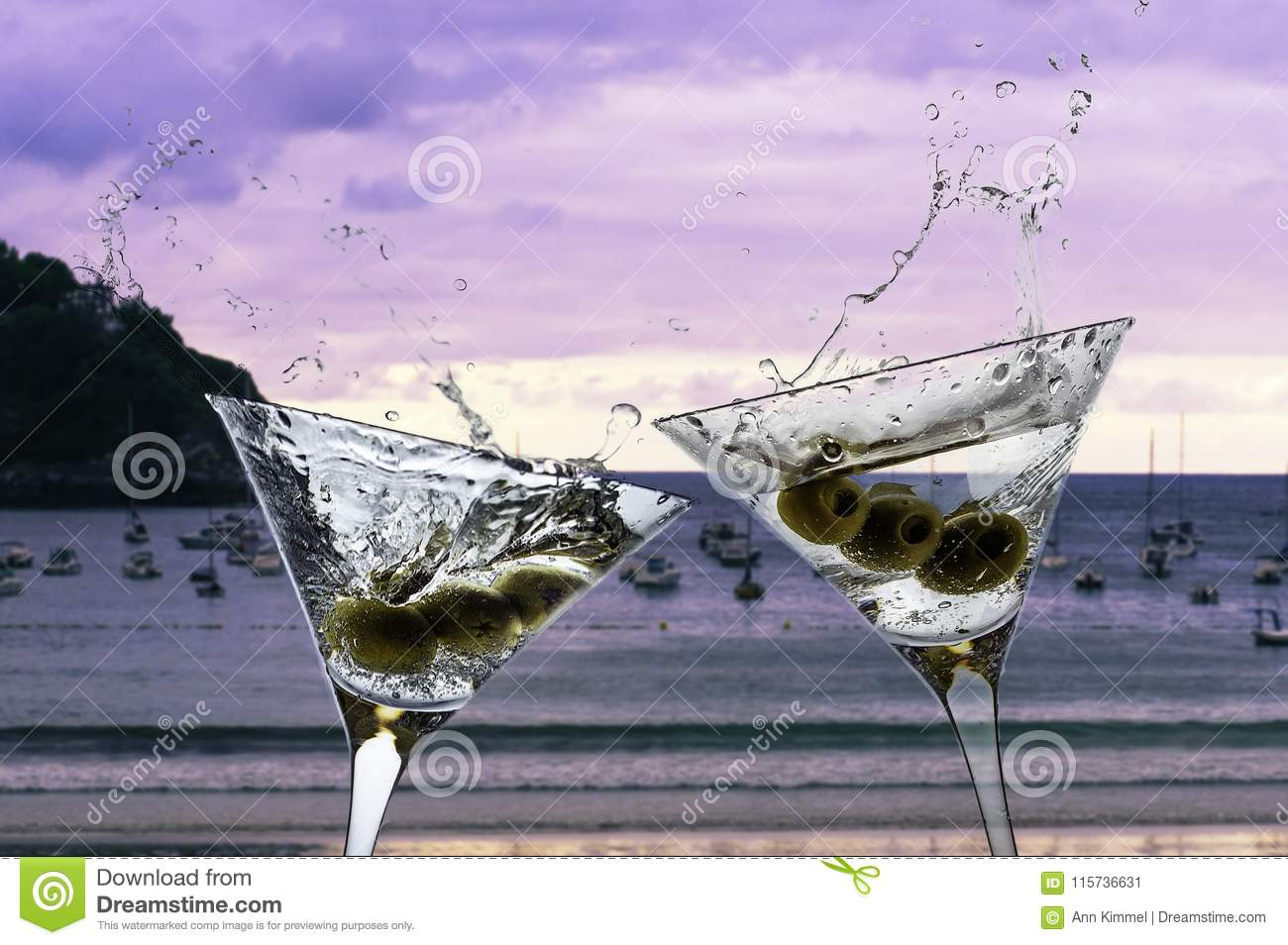 Two cocktails with splashing martini and olives on a sunset beach