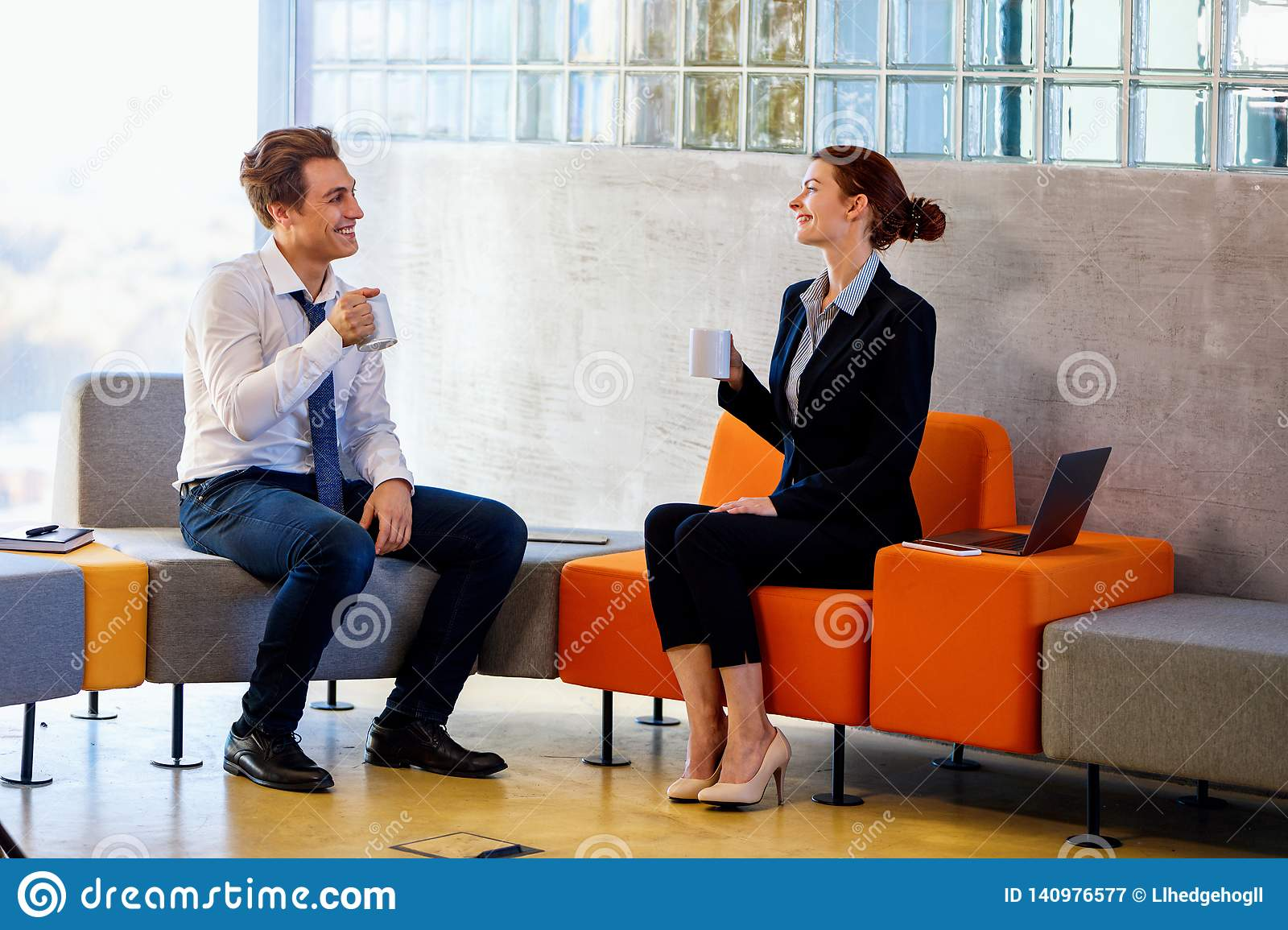 Two colleagues chatting on coffee break.
