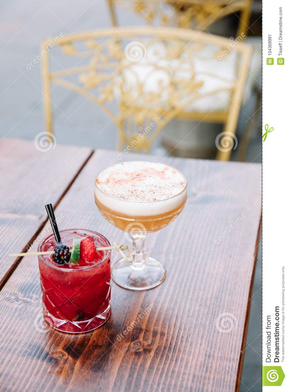 Two colorful alcoholic cocktails on a wooden table outdoors