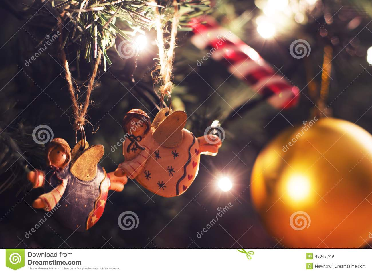 Two colorful angels hanging on christmas tree stock photo