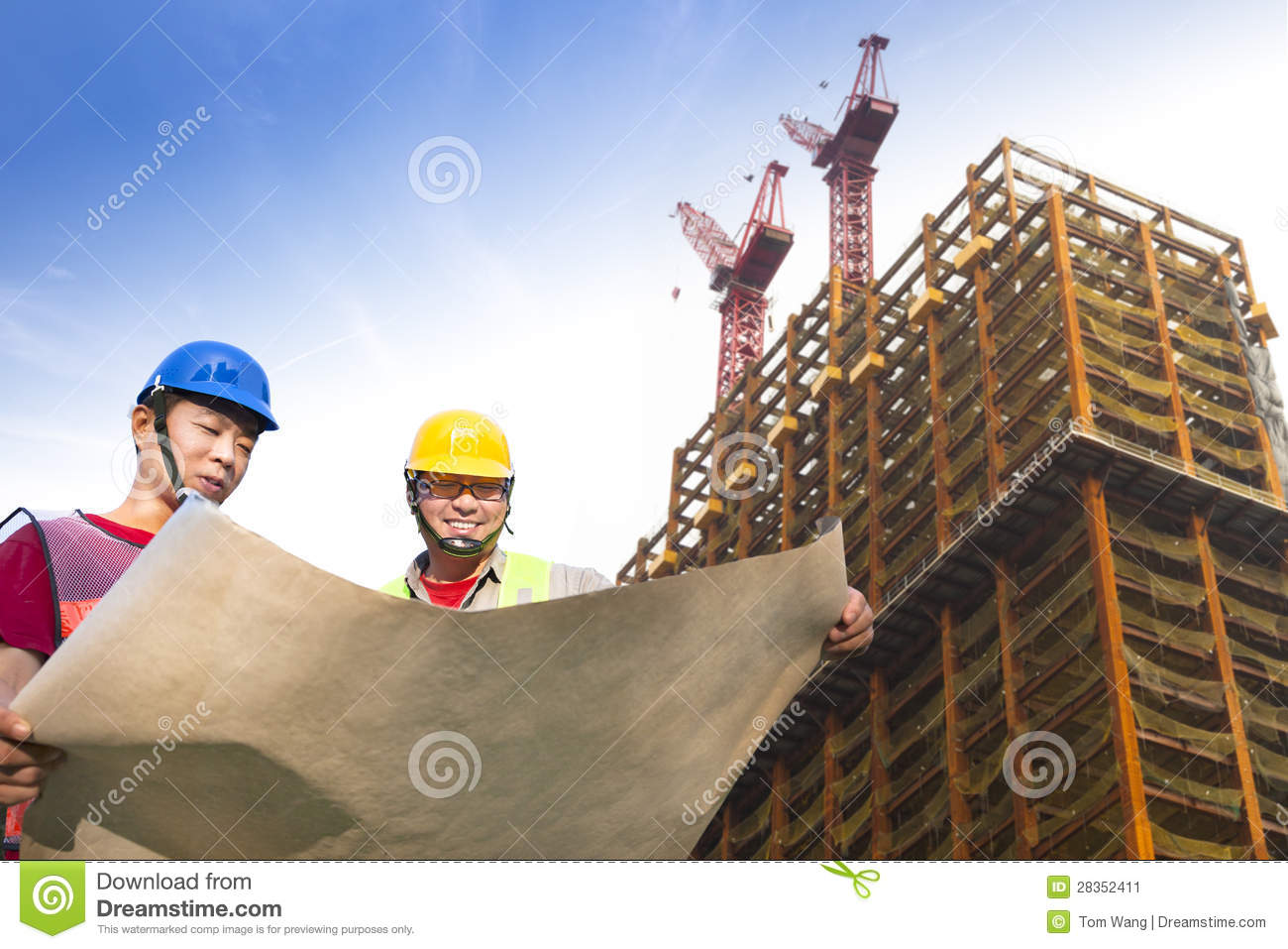 Two construction workers with building