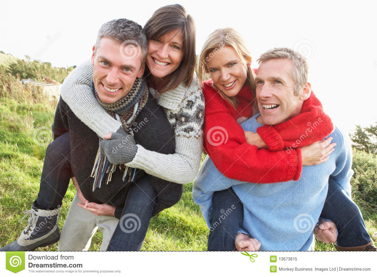 Two Couples Having Piggyback Ride In Autumn