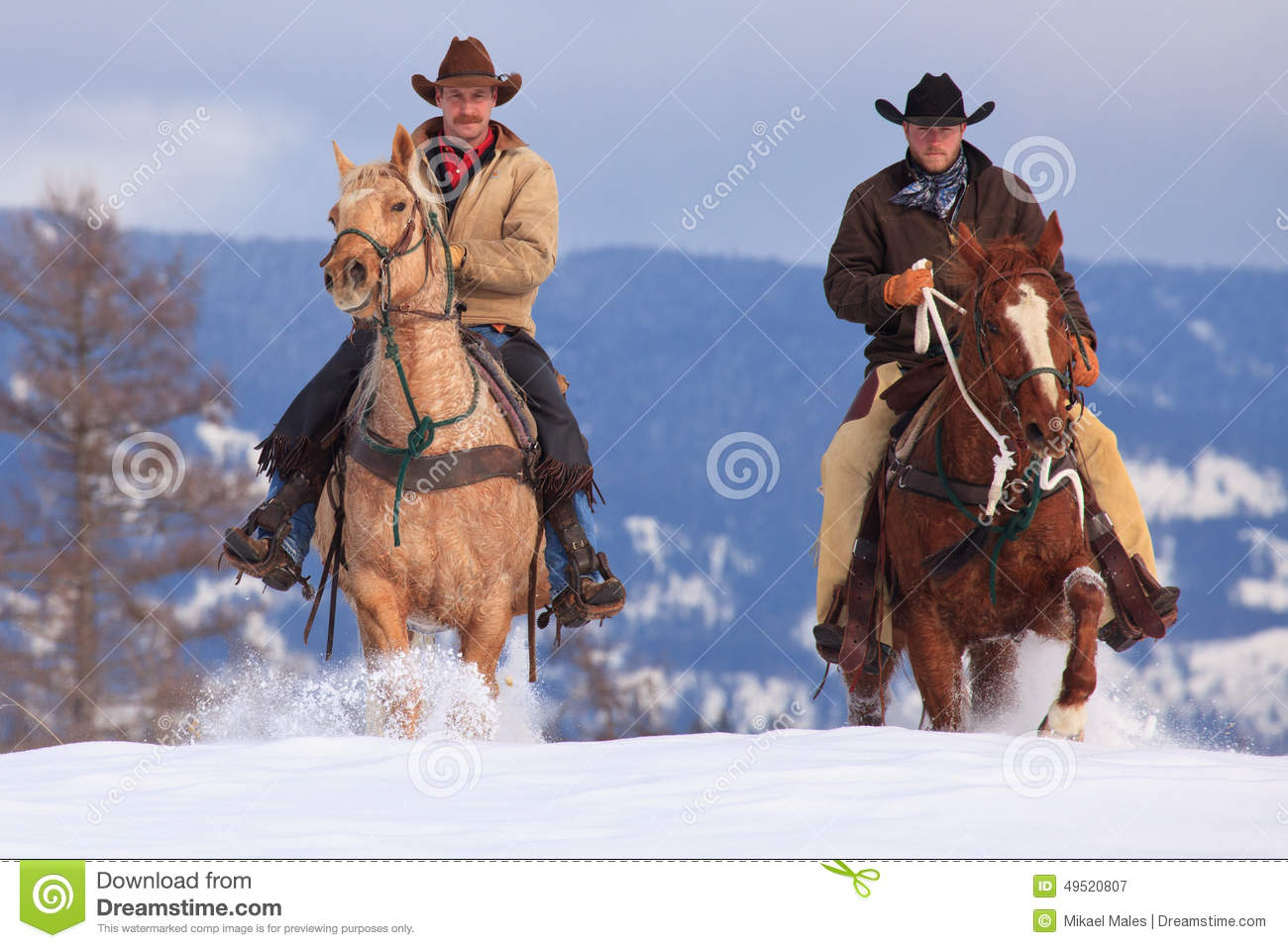 Two cowboys riding in deep snow