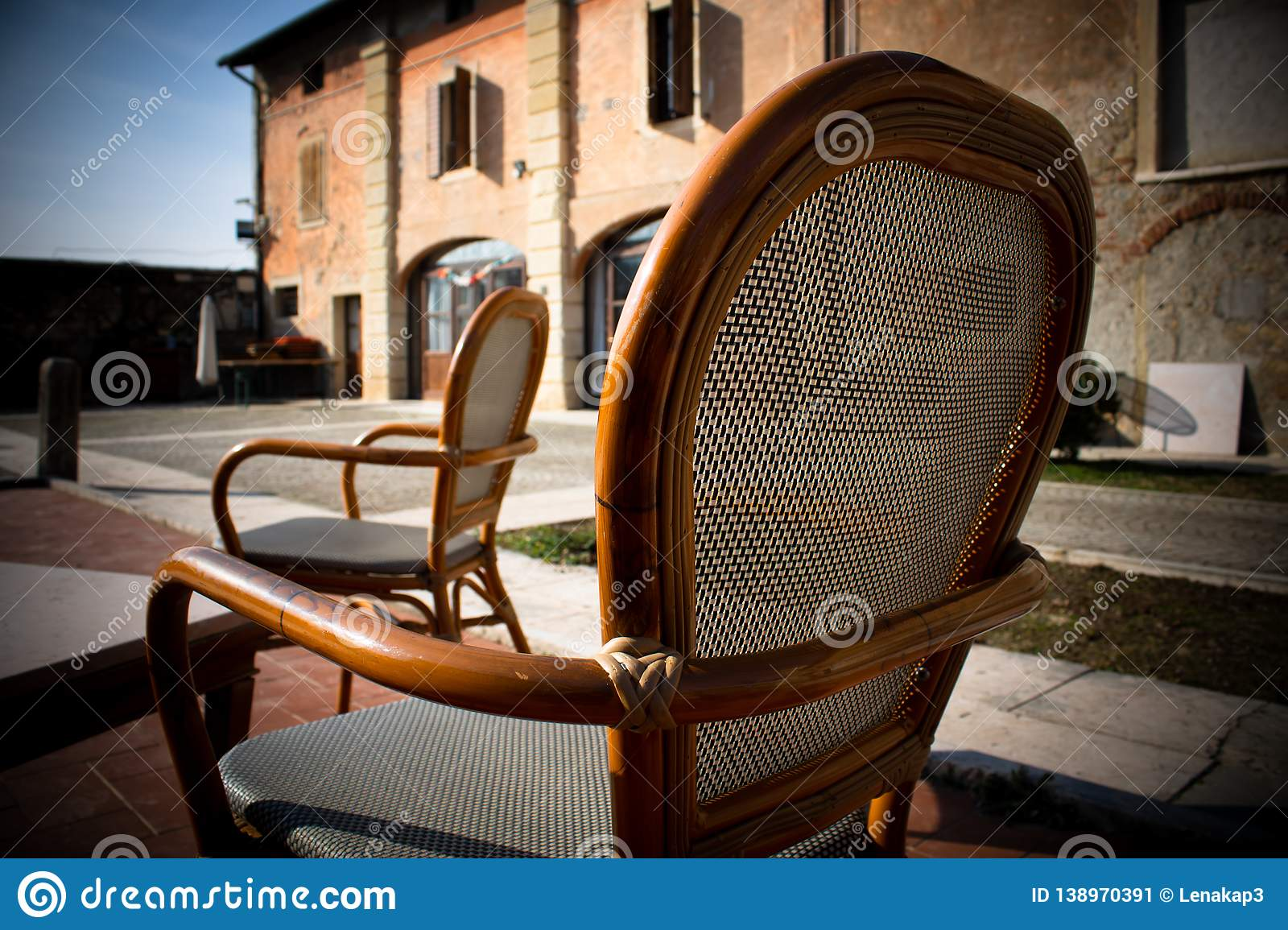 Two cozy chairs standing in the yard near the old building