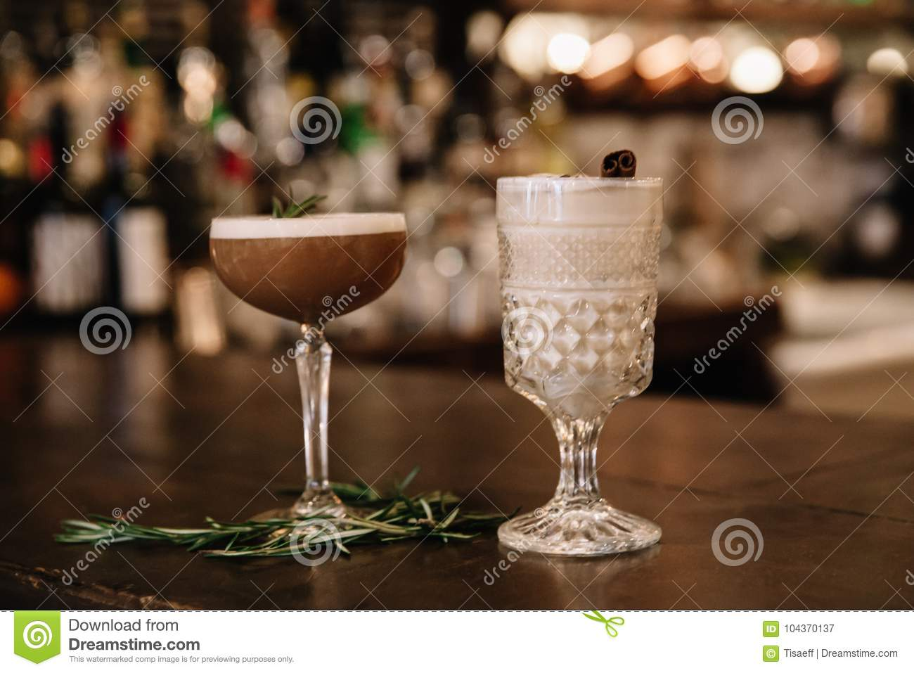 Two creamy alcoholic cocktails with a bar in the background