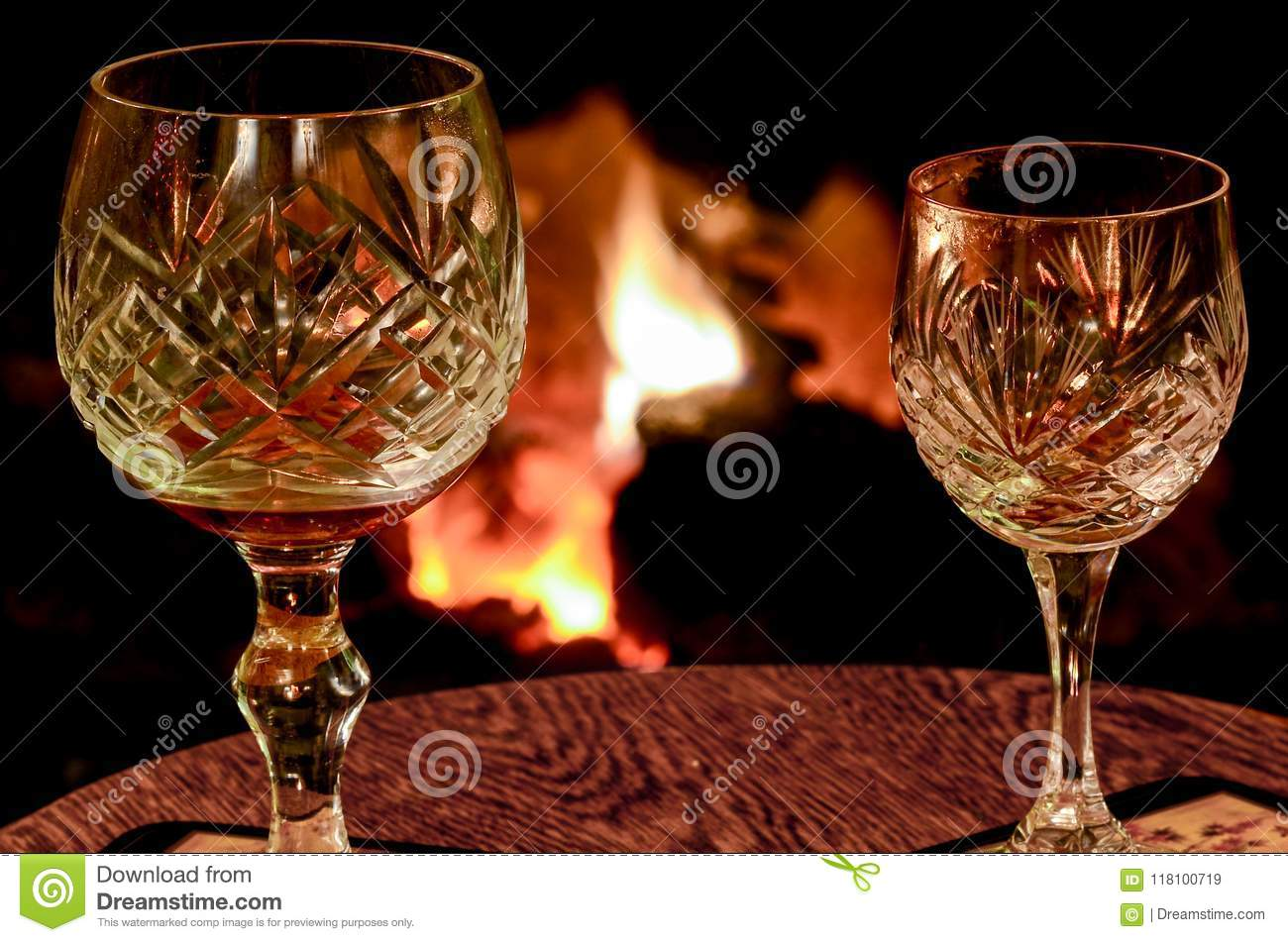 Two crystal wine glasses on a wooden table placed in front of a