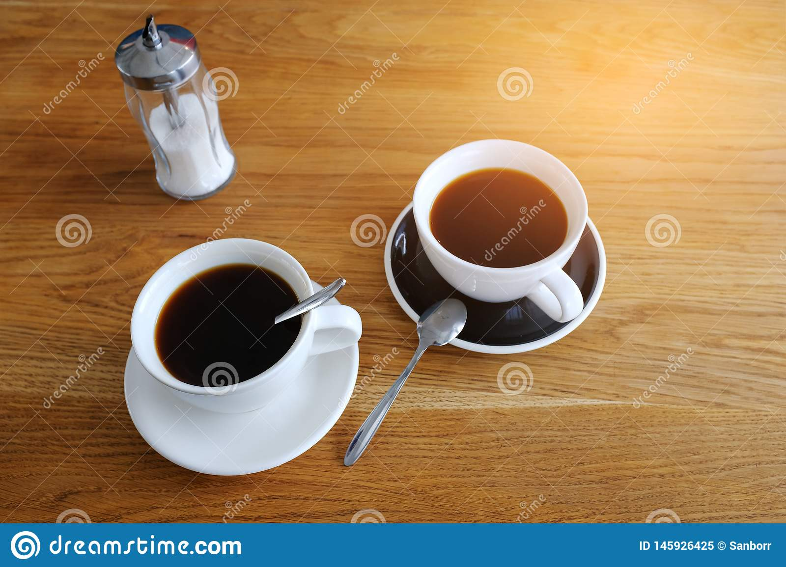 Two cups of black coffee on a wooden table, morning coffee. Business breakfast. Coffee break. Business meeting. The businessmen`s