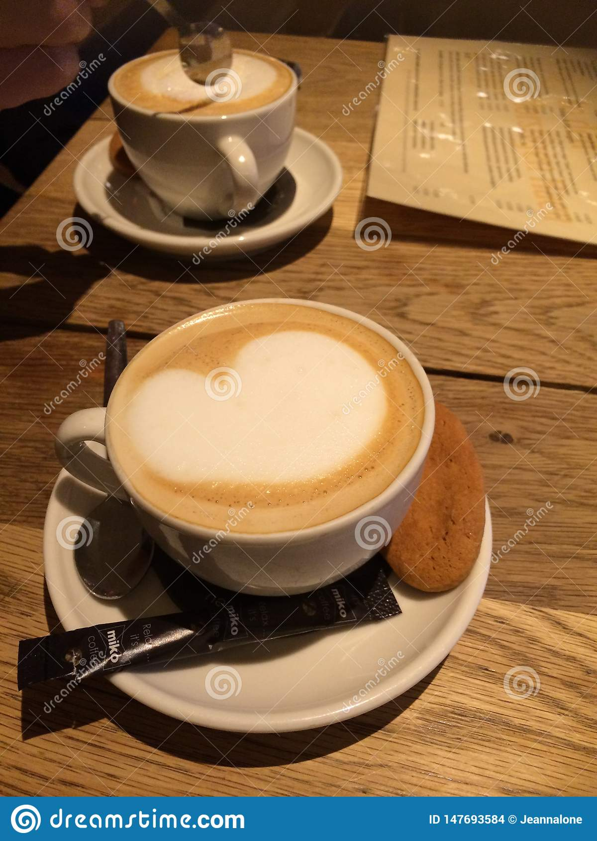 Two cups of cappuccino on a wooden table with frothy heart and a biscuit