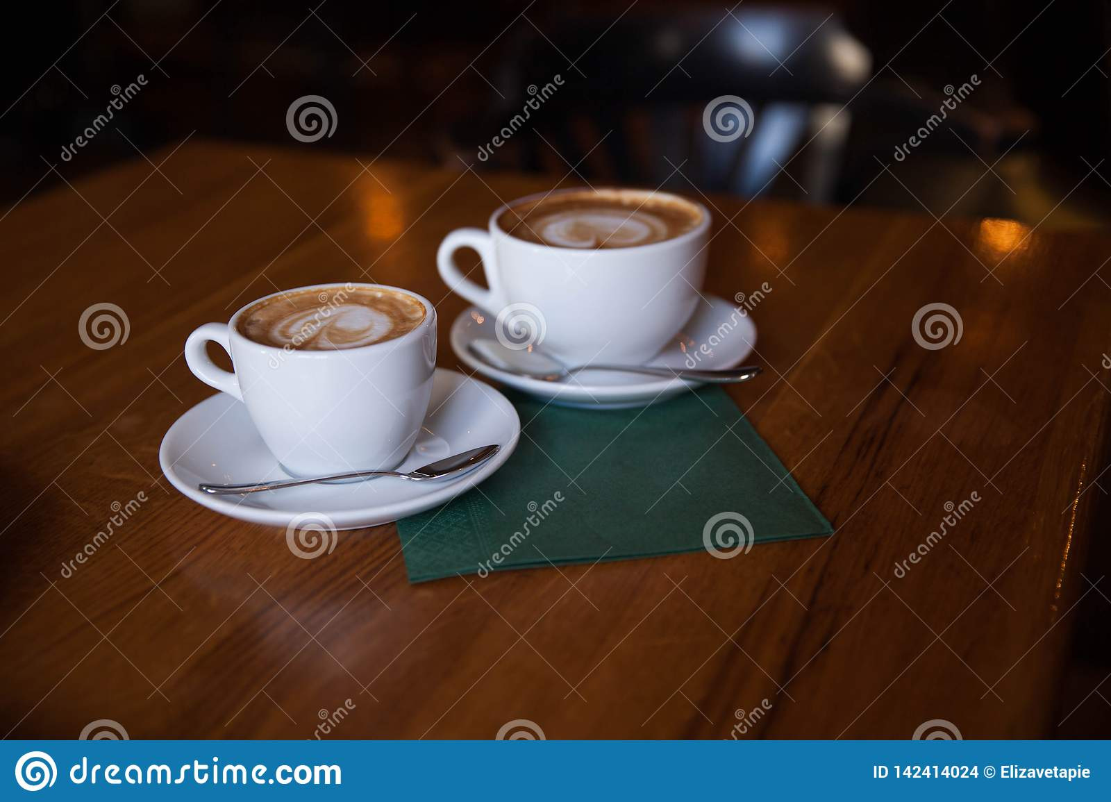 Two cups of cappuccino on a wooden table