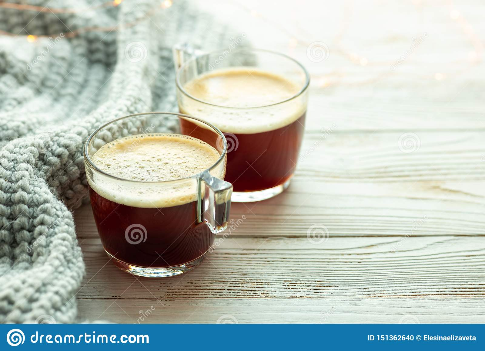 Two cups of coffee, warm knitted sweater on wooden background. Warm lights. Cozy winter morning