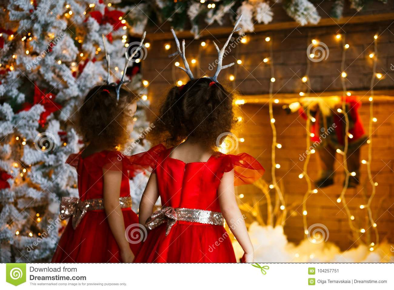 5485f7e3d Two little girls looking at the christmas fireplace near beautiful Christmas  tree. Twins in red dresses looking at Santa in fireplace.